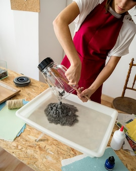 Woman putting grinded paper pulp in water over wooden desk