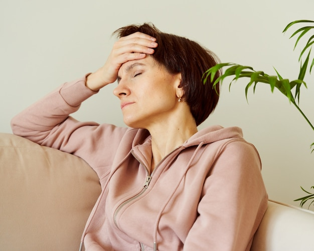 Woman putting hand on head due to headache after waking up filling deep sadness migraine