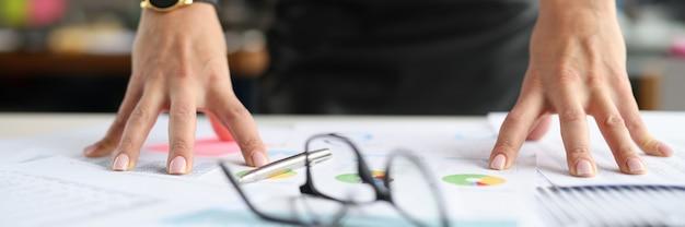 Женщина кладет руки на стол возле очков и документов с крупным планом графиков, делая важным