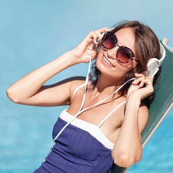 Woman putting on headphones laying on lounge
