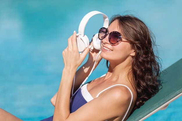 Woman putting on headphones laying on sunbed