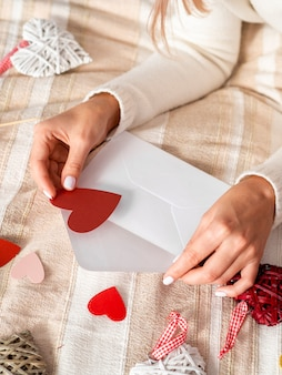 Woman putting hearts in envelope