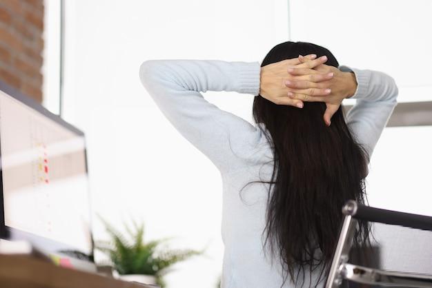 仕事のコンセプトでオフィス休憩のテーブルで頭の後ろに彼女の手を置く女性