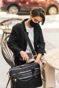 Donna che mette il suo computer portatile nella sua borsa