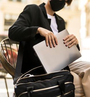 Женщина кладет ноутбук в сумочку