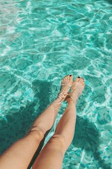 プールに足を入れている女性