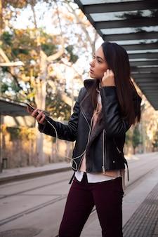Woman putting on her telephone earphones