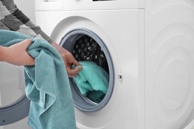 Женщина кладет белье в стиральную машину, крупным планом