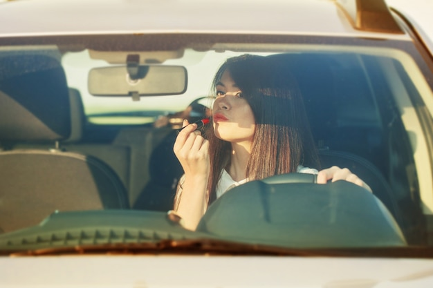Woman putting lipstick in the car before date
