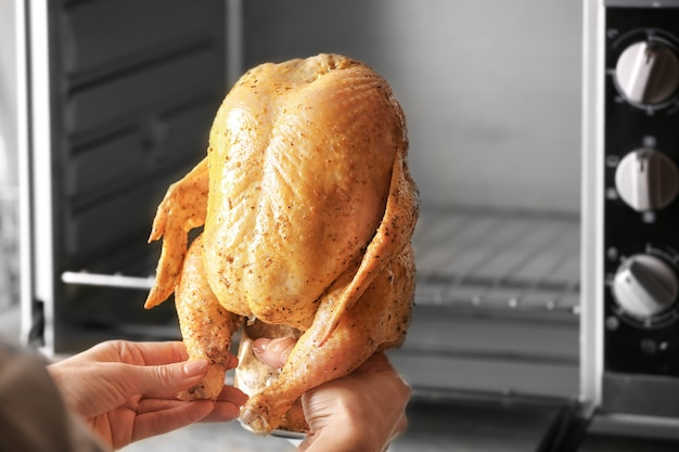 Woman putting marinaded chicken on beer can into oven