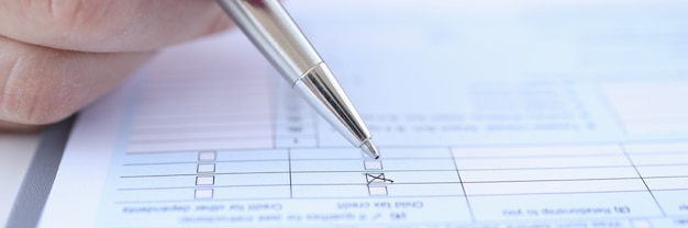 Woman putting mark with ballpoint pen on questionnaire closeup