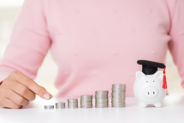 Woman putting money coin on stack of coins and piggy bank with graduation cap