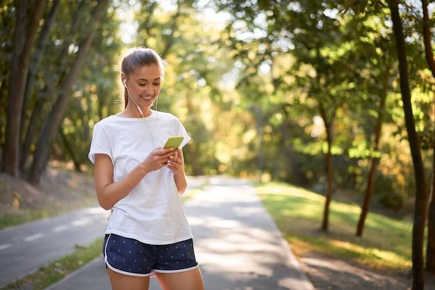 Женщина надевает наушники, чтобы послушать музыку перед бегом в летнем парке