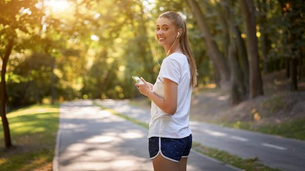 여름 공원 조깅하기 전에 음악을 듣기 위해 이어폰을 착용하는 여자
