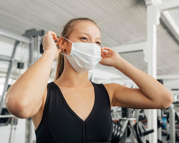 Женщина надевает медицинскую маску в тренажерном зале