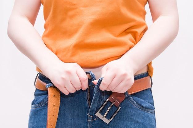 ベルト付きジーンズを履く女性