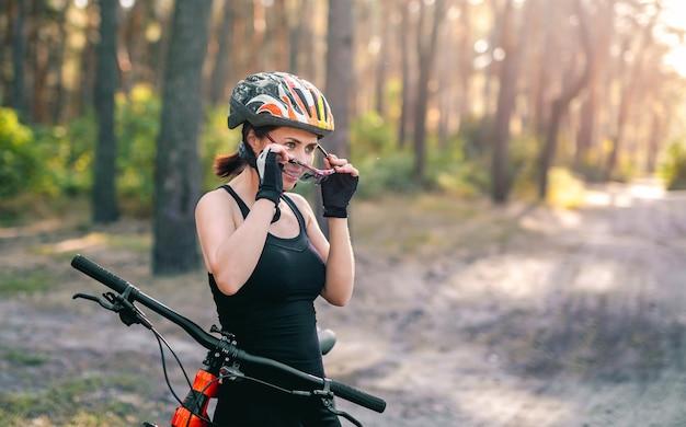 맑은 숲에서 자전거 근처 스포츠 안경에 여자