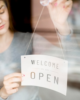 Woman putting open sign on window for coffee shop