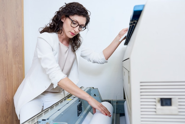 Woman putting paper into printer