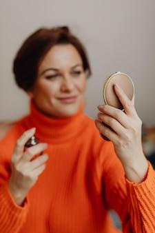 Woman putting on perfume