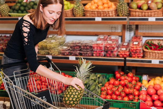 Woman putting a pineapple in the cart