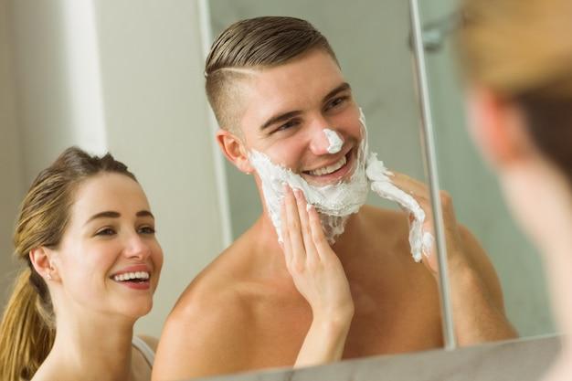 Woman putting shaving foam on boyfriends face