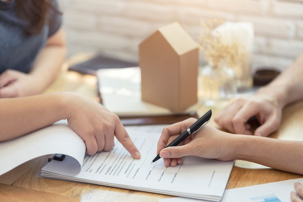 Woman putting signature on document contract, real estate purchase