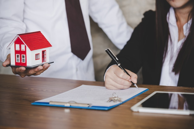 Woman putting signature on document loan contract