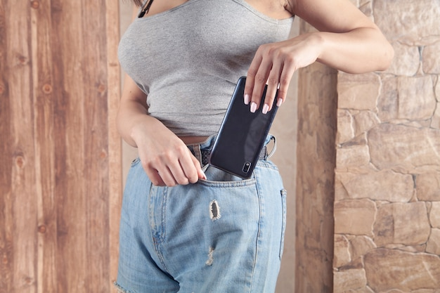 Woman putting smartphone in pocket of jeans.