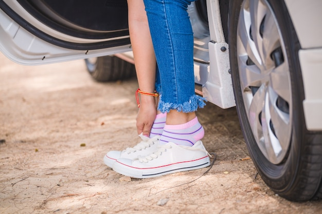 Woman putting on sneakers in car on the side of the road