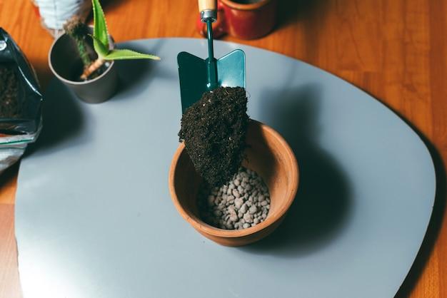 小石の入った鍋に地面を置く女性