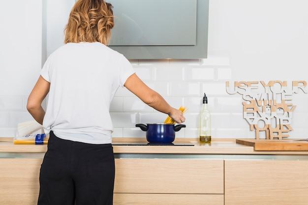 Woman putting spaghetti in pan on stove