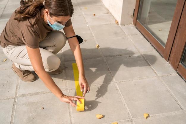 社会的距離を置くために屋外の床にテープを貼る女性