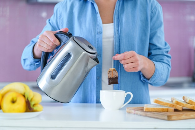 Woman putting tea bag in a cup and using an electric kettle for brewing hot tea at home at kitchen