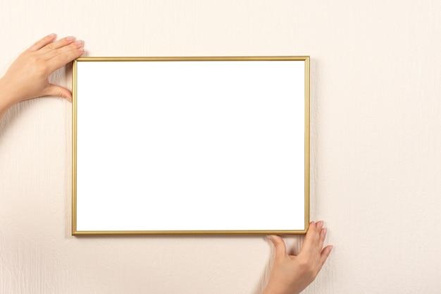 壁にフレームを立てる女性。手の絵のフレームが壁に掛かっています。
