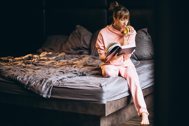 Woman in pygama sitting in bed and reading book