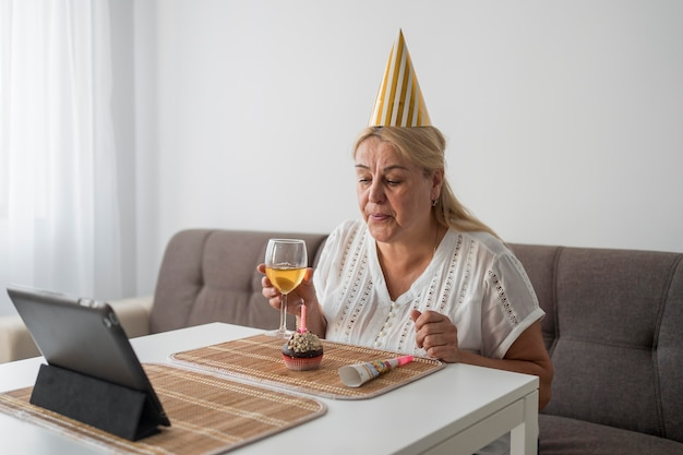 Woman in quarantine celebrating birthday with friends on laptop