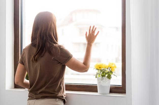 Donna in quarantena a casa guardando attraverso la finestra