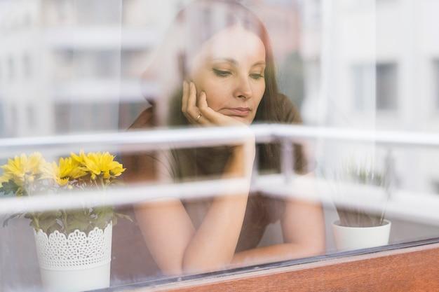 Donna in quarantena guardando attraverso la finestra