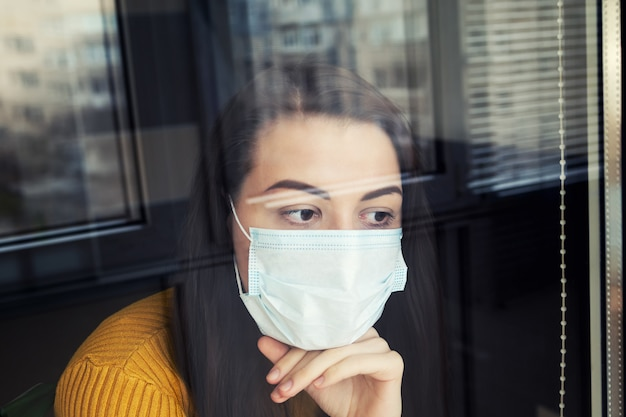 Woman in quarantine wearing protective mask.