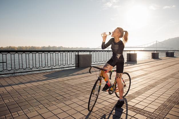 自転車に乗っている女性が喉の渇きを癒す
