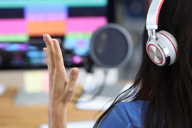 여성 라디오 발표자는 헤드폰 라이브 컨셉으로 모니터 앞에 앉아 있습니다.