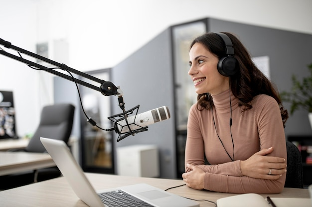 Woman in a radio studio with microphone and laptop