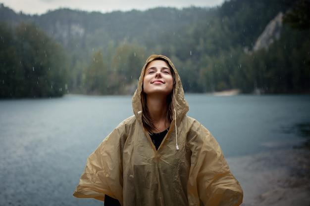 Woman in raincoat near lake in rainy day.