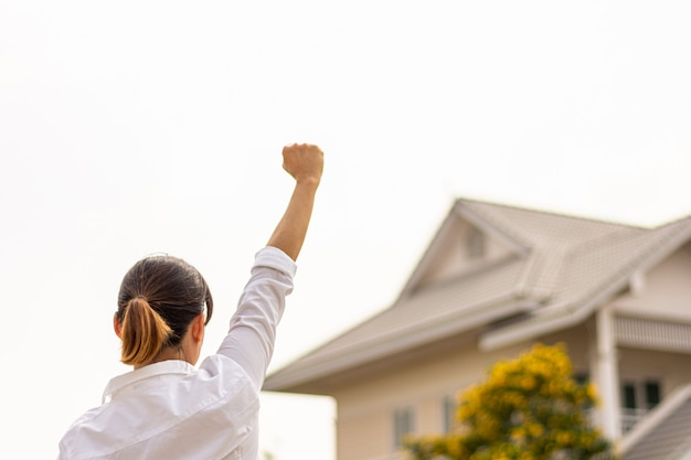 Woman raise hands to show success front a home. buy house and real estate concept.