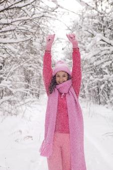 女性はピンクの服を着て森の中の小道に立って手を上げますジャケットはニットのスカーフと帽子は冬の雪の森に立っています