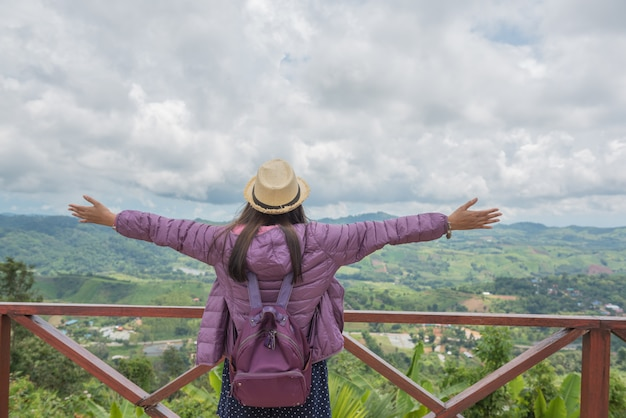 Woman raised arm up on the mountain, back view, nature travelling concept.