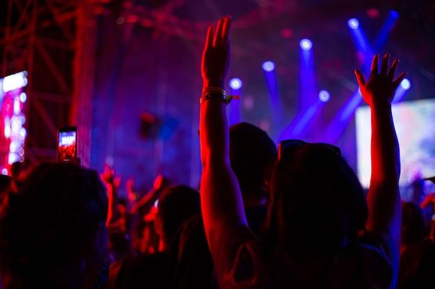 여자는 콘서트에서 그녀의 손을 들었다