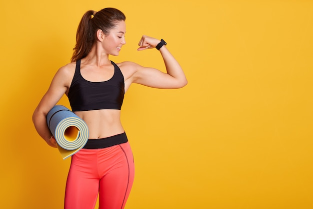 Woman raises arm and showing muscles after training, holding karemat, like to workout in gym with coach, dresses sportswear