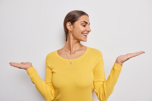여성은 손바닥을 들고 두 가지 옵션 중에서 선택합니다. 흰색 바탕에 캐주얼한 노란색 점퍼를 착용하는 척